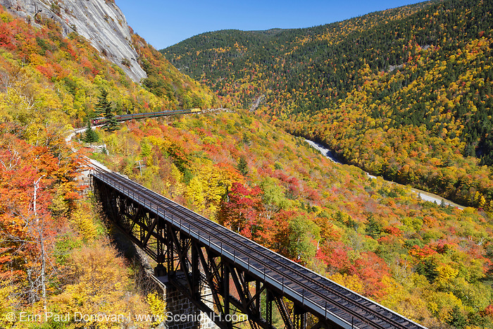"Conway Scenic Railroad's ""Notch Train"" along the old Maine Central Railroad in Hart's Location, New Hampshire during the autumn months. This trestle is within Crawford Notch State Park. And since 1995 the Conway Scenic Railroad, which provides passenger excursion trains has been using the track."