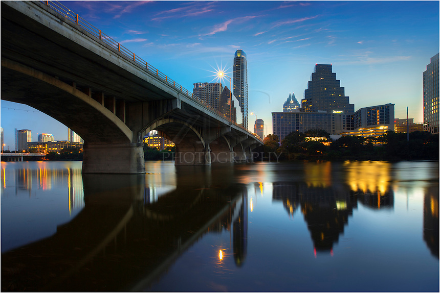 On a peaceful May morning, the Austin skyline wakes up to the first light of sunrise. Beneath Congress Bridge, Town Lake (also known as Ladybird Lake) flows to the east. In the distance, the tip of the Austin icon, the Frost Tower, can be seen, as well as the tallest building in Austin, the Austonian.