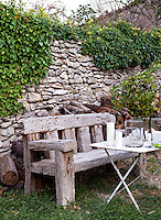 A garden bench constructed from massive beams of antique wood is placed in front of an ivy-clad stone wall