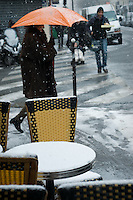 Snow on chairs and tables outside a Paris cafe.