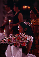 Zapotec Indian girl attends communion before her Quinceañera, the Latina coming-of-age celebration on a girl's 15th birthday. The birthday celebration begins with communion in the cathedral as she kneels during the prayer holding a candle. About 90 percent of Mexicans are Roman Catholic followers.