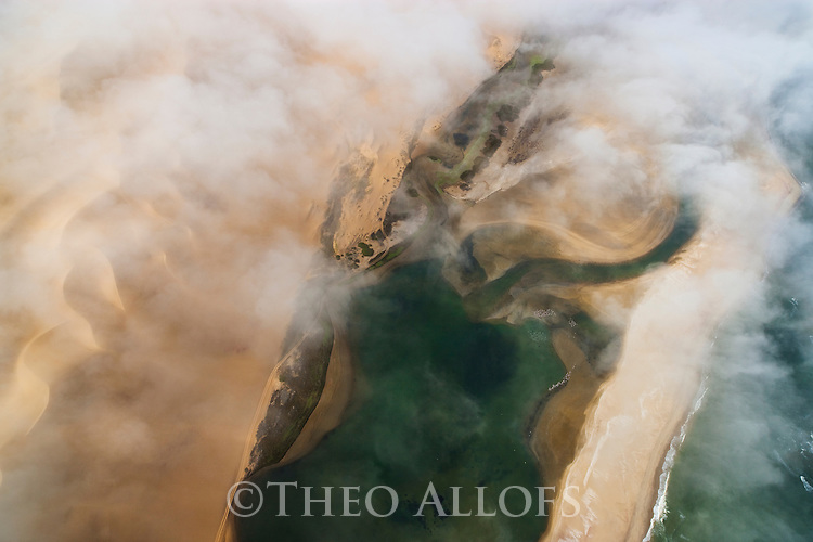 Namibia, Namib Desert, Skeleton Coast, aerial view of sand dunes and Atlantic Ocean; coast partly covered in fog