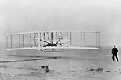 """KITTY HAWK, N.C. -- On his third attempt, Orville Wright takes the Wright Flyer for a 12-second, sustained flight December 17, 1903.  This is the first successful, powered, piloted flight in history. After months of studying how propellers work, the Wright brothers design a motor and an aircraft body strong enough to accommodate its weight and vibrations. When built, the craft weighed more than 700 pounds. This becomes the first """"Flyer."""".Credit: U.S. Air Force via CNP.Credit: U.S. Air Force via CNP"""