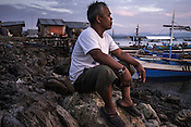 Ernesto Betasolo sits on the rocks by the beach as the sun sets in Puerto Princesa, Palawan in the Philippines. <br /> Photo: Sanjit Das/Panos for Greenpeace