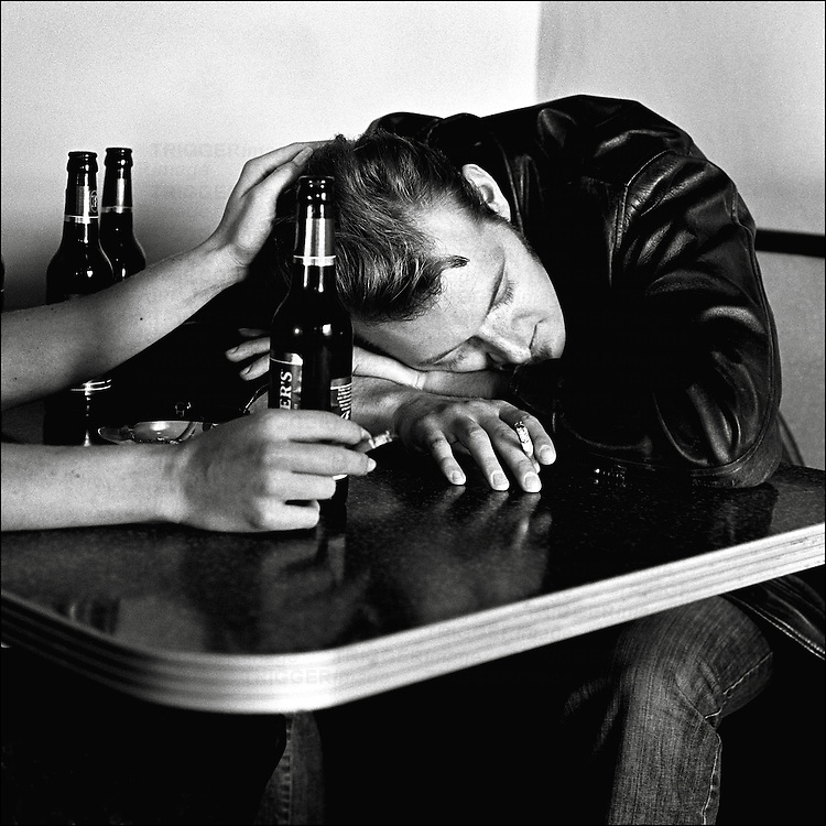 A young man wearing a leather jacket smoking a cigarette with empty beer bottles on a table