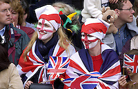 Young girls in the crowd have faces painted with flag of St George and Union Jack flags to show their patriotism, England, UK