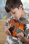 A young boy plays his guitar or ukulele