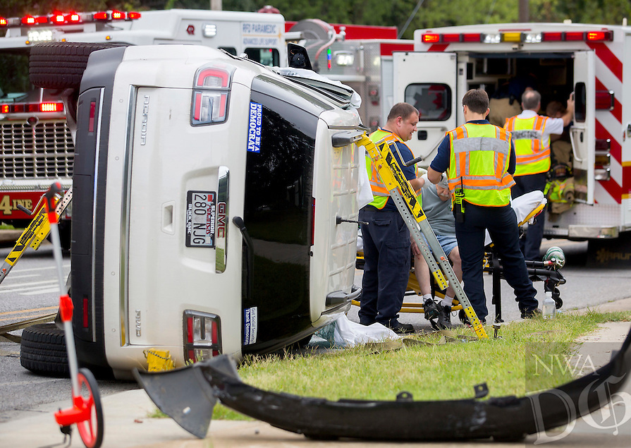 Rogers Fire Paramedics treat the drivers on Wednesday, Aug. 31, 2016, following an accident at the intersection of W. Oak Street and S. Dixieland Road. The driver of the white GMC Acadia (shown) ran a stop light while making a turn south onto Dixieland from Oak and collided with a black Chevrolet Trailblazer.