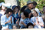 "Members of the public react after a mounted archer hits his target during the ""yabusame-shinji"" mounted archery ritual on the 3-day Reitaisai grand festival in Kamakura, Japan on  16 Sept. 2012.  Thousands turn up to the festivals main attraction, during which archers ride at speed and attempt to hit three targets along a 250-meter course erected inside the shrine grounds. Photographer: Robert Gilhooly"