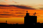 A cloud bank to the west catches the last colors of a sunset on the Great Plains west of Lincoln, NE, and silhouettes one of the many grain elevators in the area against the sky.