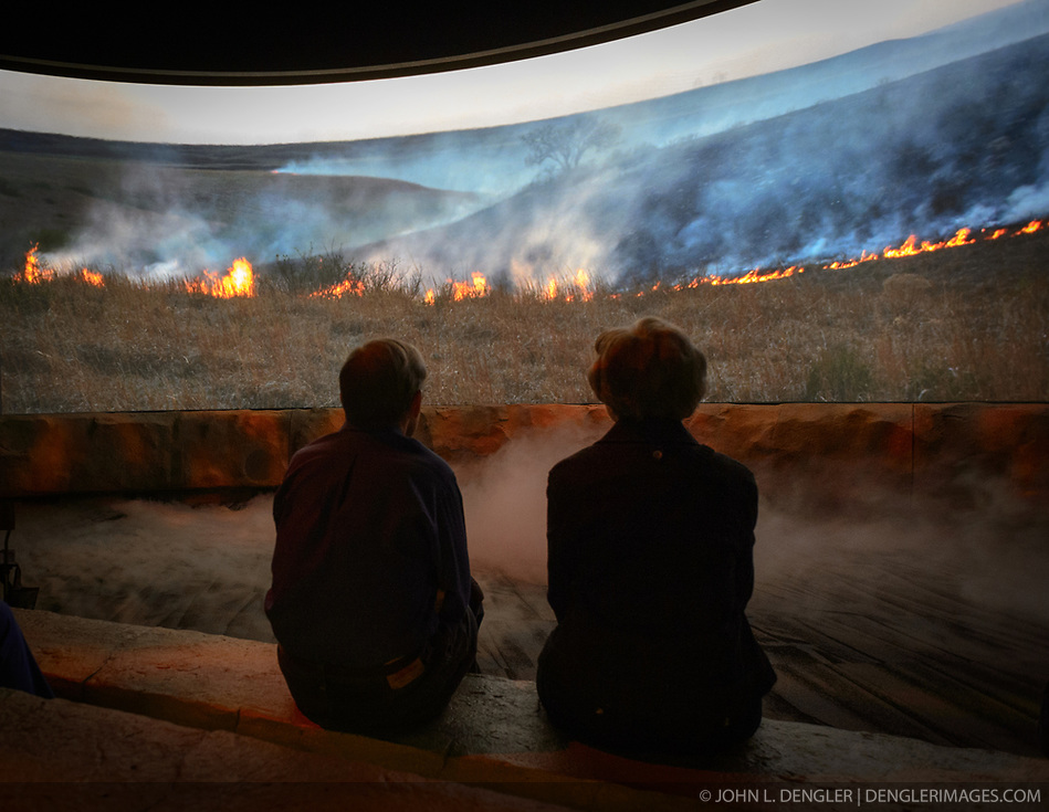 Visitors to the Flint Hills Discovery Center watch the 15-minute &lsquo;immersive experience&rsquo; film which has special effects such as smoke, fog, mist and wind which appear in the theater as the high definition film is shown on a large panoramic screen at the $24.4 million center, located in Manhattan, Kansas. This scene in the movie depicts the important role that fire plays in preserving the tallgrass prairie ecosystem. Through interactive exhibits, Flint Hills Discovery Center visitors can explore the science and cultural history of the last stand of tallgrass prairie in North America &ndash; one of the world&rsquo;s most endangered ecosystems. Other attractions of the Flint Hills Discovery Center include: an &lsquo;underground forest&rsquo; depicting the long roots of prairie plants including the 7-foot roots of bluestem prairie grass; explanations of importance of fire to the Flint Hills tallgrass prairie; and exhibits about the people and cultural history of the Flint Hills. The Flint Hills Discovery Center was designed by the museum architectural firm Vern Johnson Inc. with interpretive design and planning by Hilferty and Associates. The 34,900 square foot science and history learning center features permanent interactive exhibits, temporary exhibits, and areas for community programs and outreach activities. The Flint Hills Discovery Center received a LEED green building certification for their environmental design and energy efficiency, including their lighting and geothermal heating/cooling system.