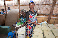 Africa, DRC, Democratic Republic of the Congo, South Kivu, Kamanyola. Women for Women project. WFW Kamanyola co-op and lifeskills training. Women making medicinal soap to sell.Sophia Asaku stacking the soap.