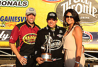 Mar. 13, 2011; Gainesville, FL, USA; NHRA top fuel dragster driver Del Worsham (center), wife Connie Worsham (right) and crew chief Brian Husen at the winners circle celebration during the Gatornationals at Gainesville Raceway. Mandatory Credit: Mark J. Rebilas-