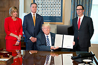 United States President Donald J. Trump holds up the order after signing the second of three Executive Orders concerning financial services at the Department of the Treasury in Washington, DC on April 21, 2017.  From left to right: US Representative Claudia Tenney (Republican of New York) US Senator David Perdue (Republican of Georgia), the President, and US Secretary of the Treasury Steven Mnuchin.<br /> Credit: Ron Sachs / Pool via CNP /MediaPunch
