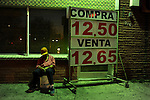 "Before sunrise a man sleeps near a ""casa de cambio"" or money exchange in Laredo, Texas on August 19, 2010. City officials say negative attitudes about the city's more dangerous sister Nuevo Laredo have kept tourists from coming and effected the over all economics of the town. Laredo also depends heavily on tourism from Mexico, as people from northern Mexico come to the border city to make purchases on merchandise like designer clothes that they cannot find cheaply in their country, but since Mexico's border region has become increasingly violent, store owners in Laredo, Texas say Mexican and American shoppers are staying home."