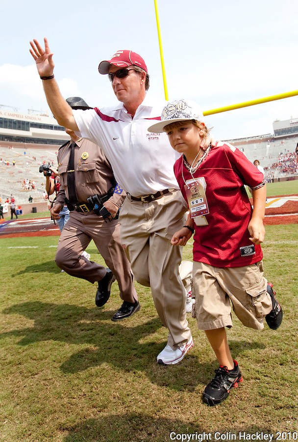 TALLAHASSEE, FL 9/4/10-FSU-SAMFORD FB10 CH-Florida State Head Coach Jimbo Fisher leaves the field with his son Trey after the Seminoles defeated Samford 59-6 to give Fisher his first victory Saturday at Doak Campbell Stadium in Tallahassee. .COLIN HACKLEY PHOTO