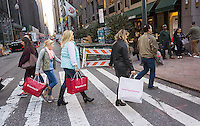 Shoppers laden with their purchases in New York on Sunday, November 20, 2016. As shoppers turn to online shopping and stores expand their opening hours into Thanksgiving fewer shoppers flocking to the stores on Friday. (© Richard B. Levine)
