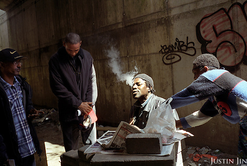 A junky in Amsterdam smokes crack as evangelists pray for him. The evangelists are former addicts. ..Victory Outreach, a controversial church started in Los Angeles in 1967, is spreading to Europe via the Netherlands. It builds its membership among junkies, prostitutes and criminals. ..Photo taken in the Netherlands in 2002. The picture is part of a photo and text documentary by Justin Jin. For more information, email justin@justinjin.com