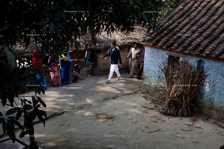 """Minister of Legislative Assembly, Ritesh Pandey, 30, campaigns door-to-door in a village with a crowd of supporters chanting slogans such as """"long live Ritesh Pandey"""" and """"press the button, decide the elephant (symbol)"""" in Ajanpara, Ambedkar Nagar, Uttar Pradesh, India, on 21st January, 2012. Returning 1.5 years ago after almost 10 years abroad, Pandey is contesting on behalf of the Bahujan Samaj Party (BSP), a party that is based on its appeal to Dalit voters. Party leader Mayawati, herself a Dalit, has recently been giving out more tickets to muslims and high caste candidates in an attempt to woo a larger spectrum of voters in Uttar Pradesh, a Bellwether state. Photo by Suzanne Lee for The National (online byline: Photo by Szu for The National)"""