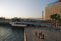 The Star Ferry terminal, bus terminus and taxi rank at Tsim Sha Tsui in late afternoon sun. Hong Kong's tallest building, the International Commerce Centre, can be seen under construction in the distance