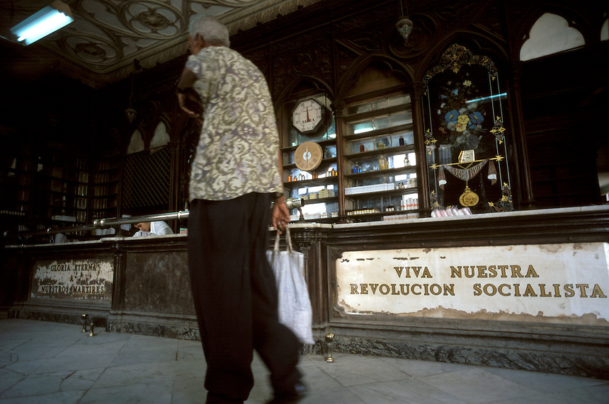 Customers of a state pharmacy pass an aging slogan to pick up inexpensive prescriptions. Though prices are low in state-subsidized pharmacies, stocks are incredibly low. The ancient building is still known as Farmacia Sarra from pre-revolution days.