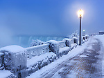 Sidewalk covered with snow and a lamp post, tranquil city scenery at Niagara Falls. Horseshoe waterfall wintertime scenic. Ontario, Canada.