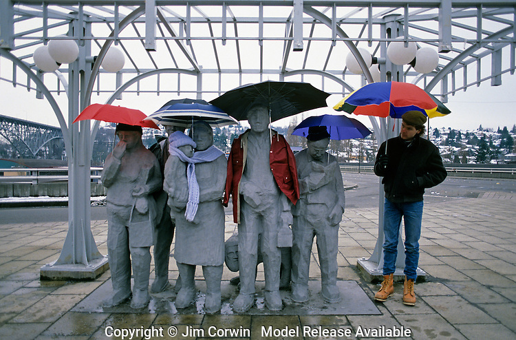 """Fremont statues """"Waiting for the Interurban"""" Artist Richard Beyer with umbrellas and jackets with another person waiting for the bus Fremont neighborhood Seattle Washington State USA   MR"""