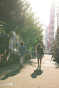 Young man and woman walking in the city in the late afternoon.