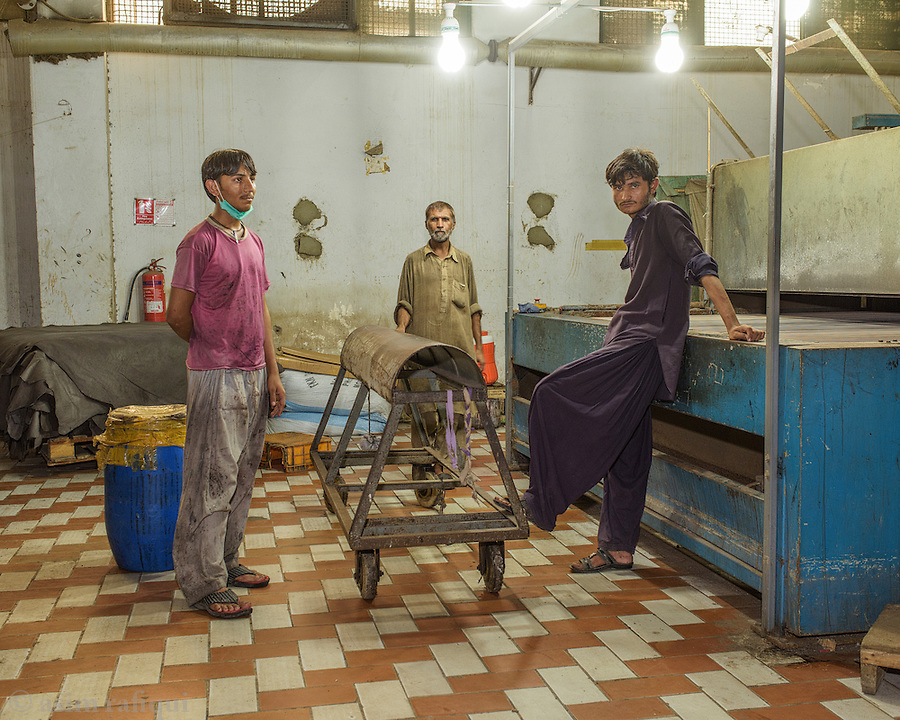Workers at a leather coloring / spraying station. The color tones added to the prepared leather are based on the requirements different customers have.
