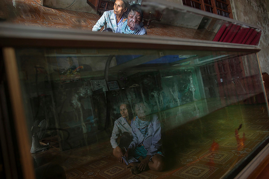 Dang Thi Quang and her son Nguyen Van Binh are reflected in aquarium in their family house in Vietnam's Quang Binh province April 11, 2015. Nguyen Van Binh was born in 1967, six years after U.S. began using the Agent Orange, with serious physical and mental health problems health officials are linking to the use of the highly toxic defoliant. His father, a soldier who served in North Vietnamese army's transportation unit, travelled and spent time in areas known as hotspots for being contaminated by the Agent Orange.  REUTERS/Damir Sagolj