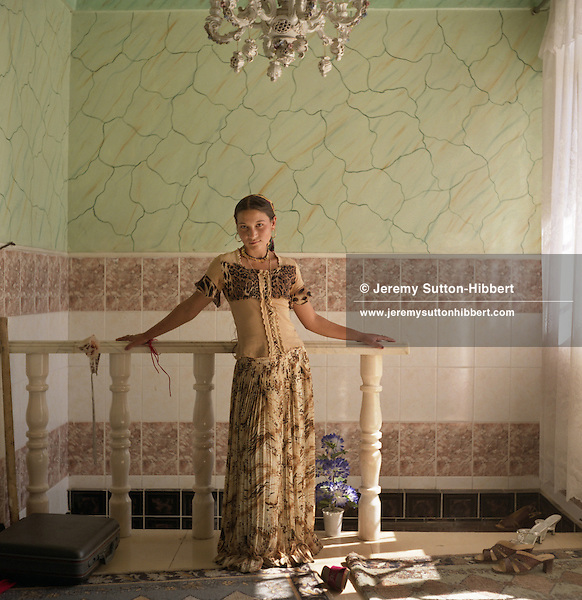 "A young, married,  Roma girl stands posing like a ""Western"" model in the hallway of her parents home. The home is one of 100 houses built in the last 7 years with the profits of scrap metal dealing, in the village of Sintesti.."