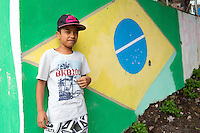 A kid poses in front of a Brazil flag painting near a small football pitch in Favela Santo Amaro in the hills around Rio de Janeiro