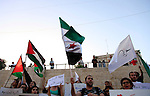 Palestinian protesters hold Syrian revolution flags during a demonstration against Syrian regime in front of Damascus gate, in Jerusalem's Old City on May 31, 2013. The EU formally modified its package of sanctions against President Bashar al-Assad's regime following this week's controversial agreement to arm Syrian rebels in line with British and French demands. Photo by Saeed Qaq