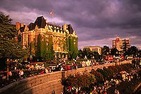 People stroll along the Inner Harbour, with the Empress Hotel in back in Victoria, Vancouver Island, British Columbia, Canada