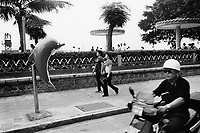 China. Guangdong province. Shantou. A couple of women walks on the sidewalk and pass near a public telephone booth, using a dolphin for the cabin. A man wearing an helmet rides his scooter on the road. Shantou, historically known as Swatow or Suátao, is a prefecture-level city on the eastern coast of Guangdong province. 20.05.04 © 2004 Didier Ruef