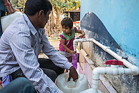 A child fills up her own drinking bottle as other villagers buy water at the iJal water station in Gorikathapalli, a remote village in Warangal, Telangana, India, on 22nd March 2015. Safe Water Network works with local communities that live beyond the water pipeline to establish sustainable and reliable water treatment stations within their villages to provide potable and safe water to the communities at a nominal cost. Photo by Suzanne Lee/Panos Pictures for Safe Water Network