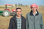 Sabah Ibrahim (left), a Christian farmer displaced by the Islamic State group in 2014, stands in a field outside Sindana, Iraq, owned by Shaalan Fathie, a Muslim. Fathie has hired Ibrahim to help him on his farm until the Christian man can safely return home. Ibrahim received some farm  machinery and additional training in its use in a livelihood program sponsored by the Christian Aid Program Nohadra - Iraq (CAPNI).