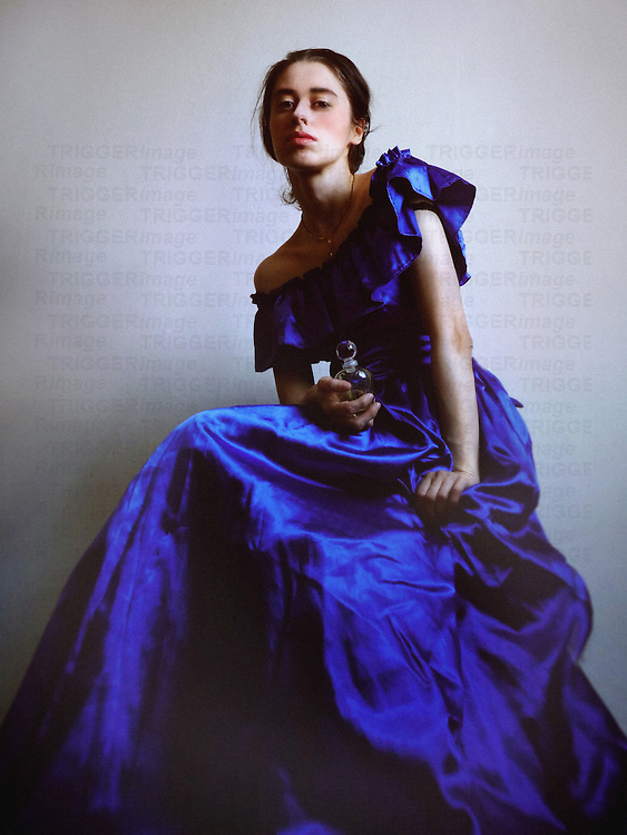 A young woman seated, in a  blue vintage evening gown, holding a little viol made of glass, with a proud expression.