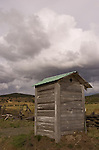 Weathered wooden outhouse with green roof, clouds in the outback of Eastern Oregon