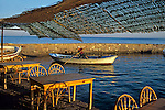 A fisherman pushes his small boat out of the harbor and past an outdoor cafe at the small coastal village of Asos,Turkey on the Aegean Coast.