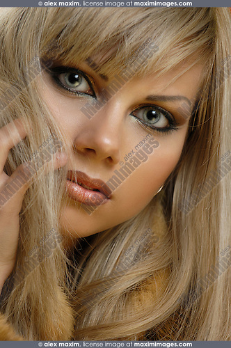 Stock photo of a Beautiful blond woman with shiny golden hair wearing a fur coat Artistic expressive close-up glamorous face portrait Make-up beauty glamour style and fashion concept Twenty year old caucasian girl