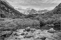 Maroon Creek flows down from the snows of Maroon Pass in summer and nourishes the valley. This black and white photograph of the Maroon Bells was taken just above Maroon Lake with Maroon and North Maroon Peak, two of Colorado's iconic 14ers, in the background. The sun had not yet risen behind me and the clouds were just beginning to show some color. Mornings like this are the reason I get out of bed at 3am and drive/hike to various locations.