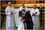 The newly married couple seal their vows with a kiss watched over by the proud clergy members conducting the service.