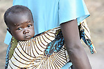 A baby appreciates the view from its mother's back in the Southern Sudan village of Ligitolo. Families here are rebuilding their lives after returning from refuge in Uganda in 2006 following the 2005 Comprehensive Peace Agreement between the north and south. NOTE: In July 2011, Southern Sudan became the independent country of South Sudan