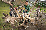 "Tsaatan children ride reindeer in the remote mountains along the border of Mongolia and Siberia. ""Tsaatan"" appropriately translates to ""reindeer people,"" as reindeer provide essential food, clothing, and transportation for this unique, endangered culture."