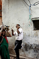 Business on the phone whilst a women toils away in the alleys of Dharavi.