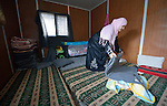 A Syrian woman folds up her family's bedding inside their shelter in the Zaatari refugee camp near Mafraq, Jordan. Established in 2012 as Syrian refugees poured across the border, the Zaatari camp held more than 80,000 refugees by 2015, and was rapidly evolving into a permanent settlement. ACT Alliance member agencies provide a variety of services to refugees living in the camp.