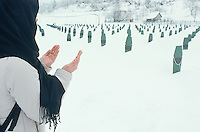 Bosnia and Herzegowina. Republika Serpska. Potocari. Potocari is a small village distant 10 km from the town of Srebrenica. Muslim graveyard. 8000 muslims men were killed on june 1995 by the serbs at the end of the bosnian war. The identity of 1337 dead men is known and they are buried in tombs in the memorial cemetery. A young muslim woman prays with both her arms open. Her fingers nails are fashionable and stylish.© 2005 Didier Ruef