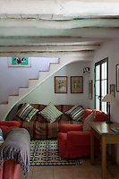 A sofa with a striped loose cover and cushions has been placed in a corner of the living room under the stairs