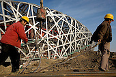 "Construction workers in Beijing build the ""Bird's Nest"" National Stadium, which will be unveiled for the 2008 Summer Olympics."